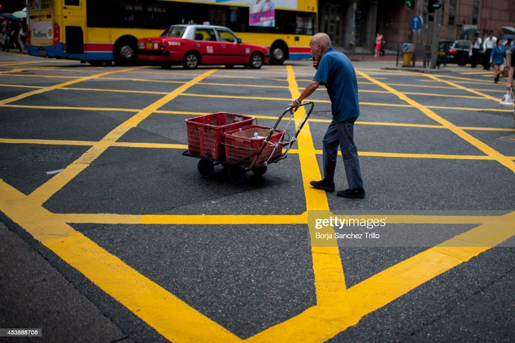 An elderly man pushes a cart though a crossroad on August 20, 2014 in Hong Kong, Hong Kong. A government-commissioned study headed by University of Hong Kong academic Nelson Chow Wing-sun proposed to fund HK $3,000 a month pension for every Hongkonger over 65, rich or poor, without a means test. The pension should be funded partly by contributions ranging from 1 to 2.5 per cent of employees' salaries, paid by employers and workers. One in three old people in Hong Kong lives below estimated poverty line some of them struggling to make a living collecting cardboard boxes and plastic bottles on the street.