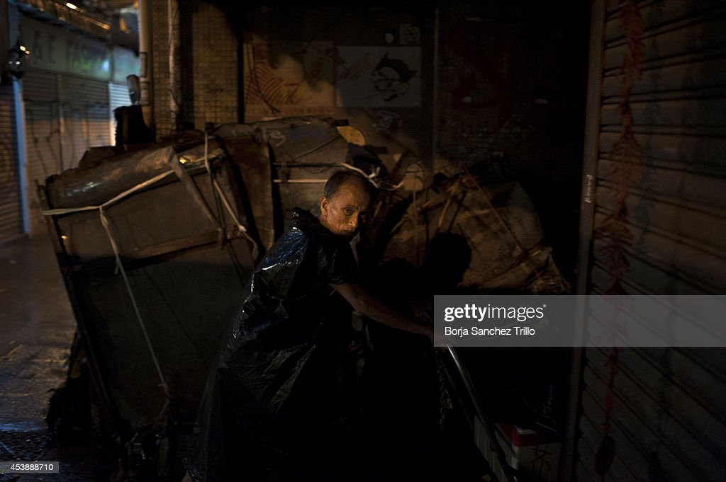 An elderly man pushes a cart through an alley on August 19, 2014 in Hong Kong, Hong Kong. A government-commissioned study headed by University of Hong Kong academic Nelson Chow Wing-sun proposed to fund HK $3,000 a month pension for every Hongkonger over 65, rich or poor, without a means test. The pension should be funded partly by contributions ranging from 1 to 2.5 per cent of employees' salaries, paid by employers and workers. One in three old people in Hong Kong lives below estimated poverty line some of them struggling to make a living collecting cardboard boxes and plastic bottles on the street.