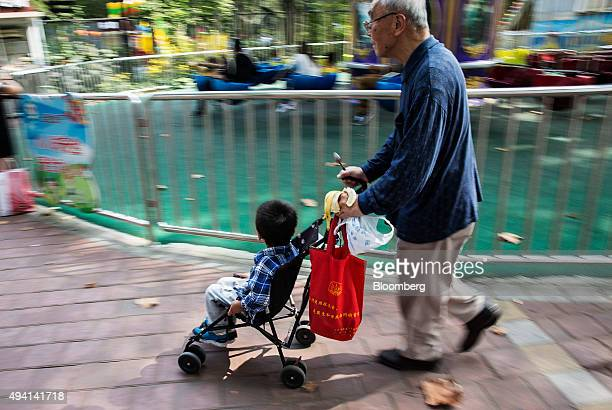 An elderly man pushes a child on a baby stroller at the Lu Xun Park in Shanghai China on Saturday Oct 24 2015 The Chinese Communist Party will...