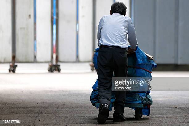 An elderly man pushes a loaded cart covered with blue tarp in a park in Tokyo Japan on Monday July 8 2013 The number of Japanese seniors living alone...
