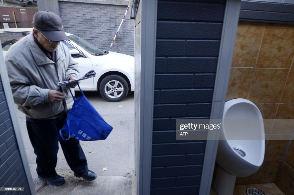 An elderly man reads a newspaper as he steps into a public toilet in Beijing on November 19, 2012. In 2001 the World Toilet Organization declared November 19 as World Toilet Day (WTD) to raise awareness on sanitation conditions worldwide. AFP PHOTO/WANG ZHAO