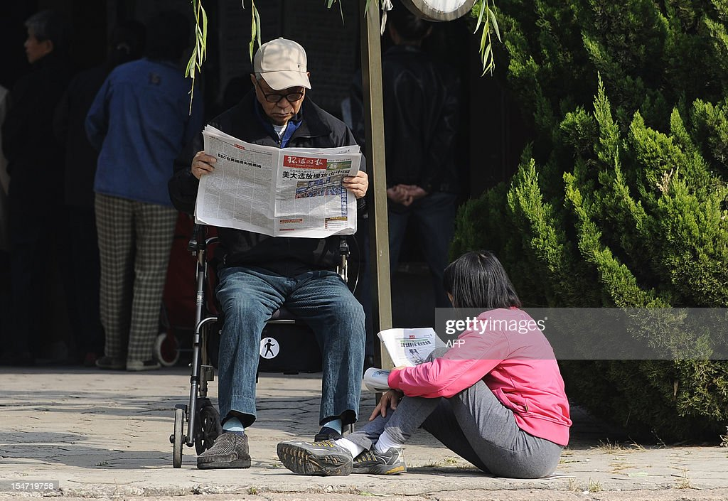 An elderly man reads the newspaper sitting on his wheelchair, accompanied by his granddaughter by a road in Beijing on October 25, 2012. China's elderly face increasing uncertainty three decades since the one-child policy took hold, with no real social safety net, the law has left four grandparents and two parents with one caretaker for old age -- and bereaved families with none.