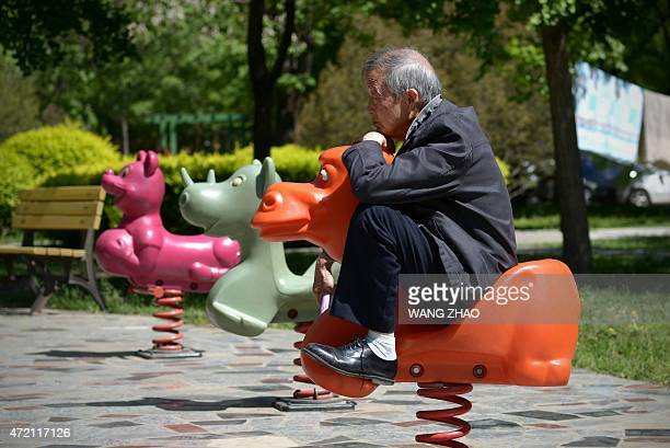 An elderly man sits on a hobby horse at a residential area in Beijing on May 4 2015 AFP PHOTO/ WANG ZHAO