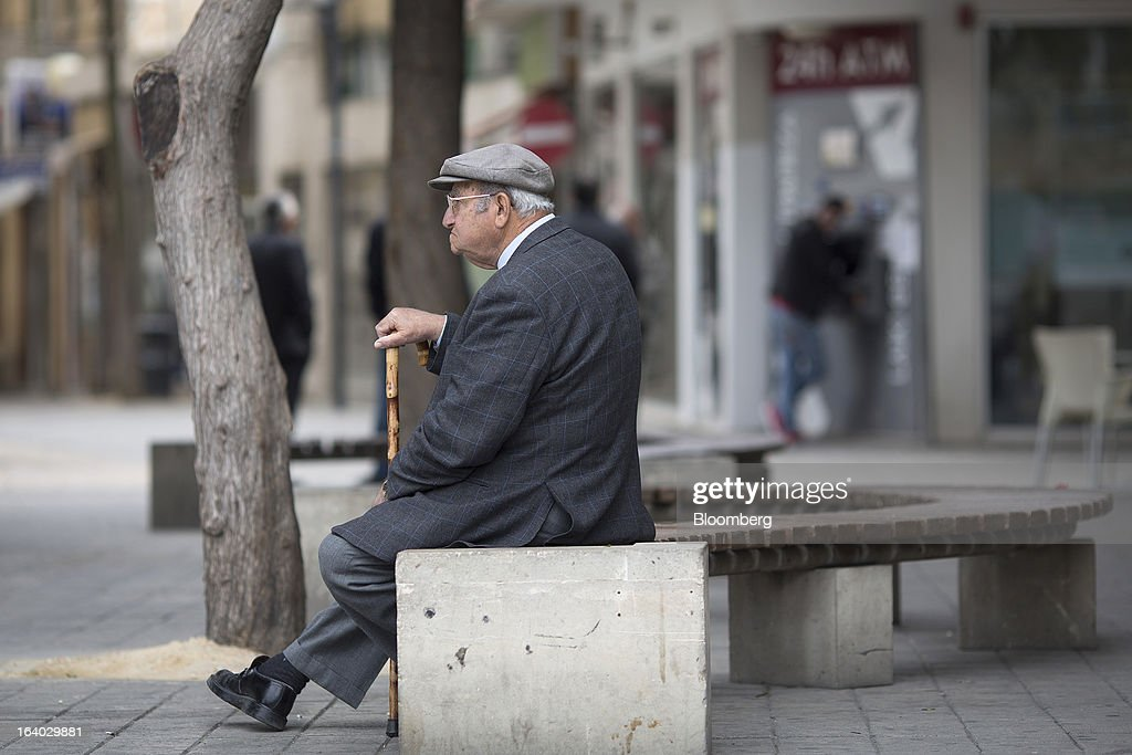 An elderly man sits on a public bench and watches media activity on a street in central Nicosia, Cyprus, on Tuesday, March 19, 2013. Euro-area finance ministers told Cyprus to raise 5.8 billion euros ($7.5 billion) from bank depositors to unlock emergency loans, maintaining the revenue target while suggesting sparing small-scale savers. Photographer: Simon Dawson/Bloomberg via Getty Images