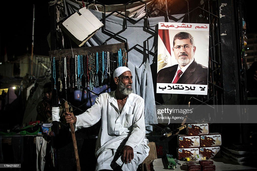 An elderly man sits with a Mohammed Morsi poster beside him on August 2, 1013 in Cairo,Egypt. Following the ousting of Egypts first democratically elected president Mohammed Morsi by the military, Mohammed Morsis supporters started a series of protests in various cities of the country.