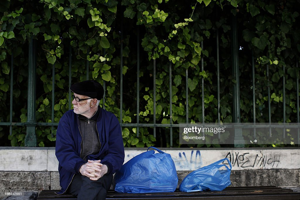 An elderly man sits with his shopping bags on a bench in the national gardens in Athens, Greece, on Thursday, Nov. 15, 2012. Greece's Supreme Court of Audit ruled that Greek austerity measures including cuts to pensions and an increase in the retirement age may be unconstitutional, state-run Athens News Agency reports, without citing anyone. Photographer: Kostas Tsironis/Bloomberg via Getty Images