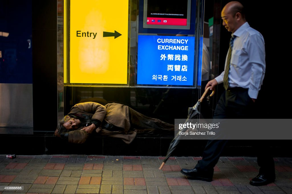 An elderly man sleeps in front of a bank on August 19, 2014 in Hong Kong, Hong Kong. A government-commissioned study headed by University of Hong Kong academic Nelson Chow Wing-sun proposed to fund HK $3,000 a month pension for every Hongkonger over 65, rich or poor, without a means test. The pension should be funded partly by contributions ranging from 1 to 2.5 per cent of employees' salaries, paid by employers and workers. One in three old people in Hong Kong lives below estimated poverty line some of them struggling to make a living collecting cardboard boxes and plastic bottles on the street.