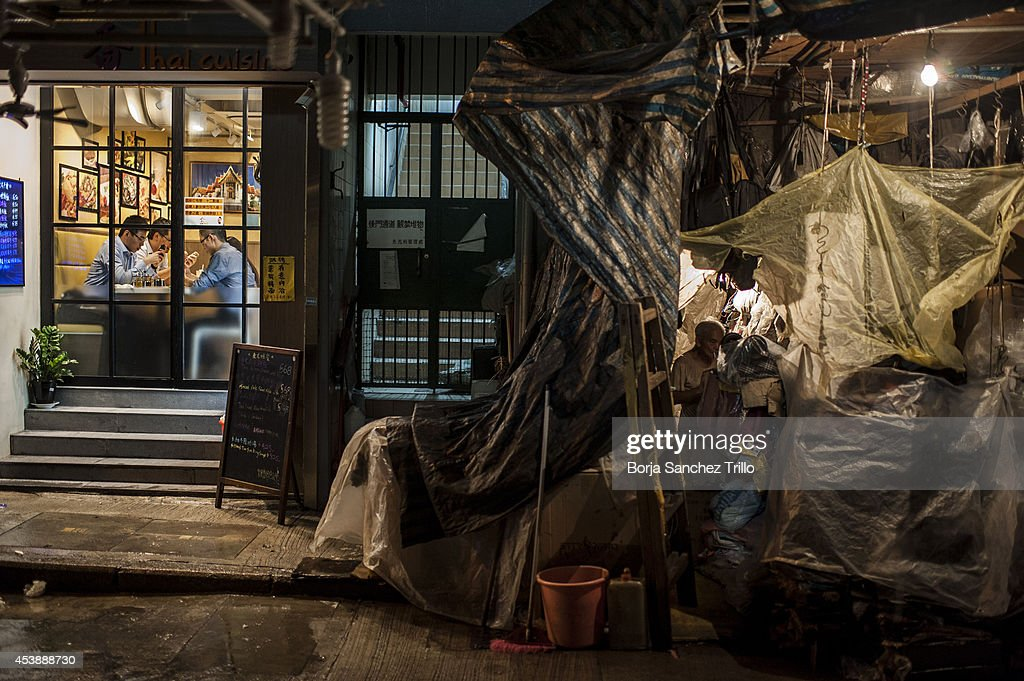 An elderly man smokes inside his home-shop on August 19, 2014 in Hong Kong, Hong Kong. A government-commissioned study headed by University of Hong Kong academic Nelson Chow Wing-sun proposed to fund HK $3,000 a month pension for every Hongkonger over 65, rich or poor, without a means test. The pension should be funded partly by contributions ranging from 1 to 2.5 per cent of employees' salaries, paid by employers and workers. One in three old people in Hong Kong lives below estimated poverty line some of them struggling to make a living collecting cardboard boxes and plastic bottles on the street.