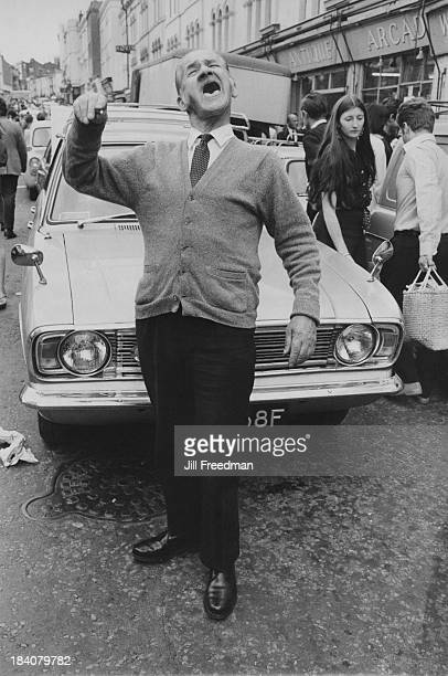 An elderly man stands amongst the people shopping in Portobello Road London 1969