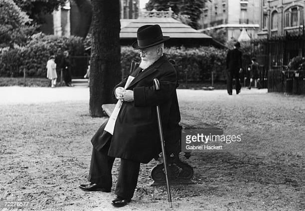 An elderly man takes a nap on a bench in the garden of Notre Dame cathedral Paris circa 1950