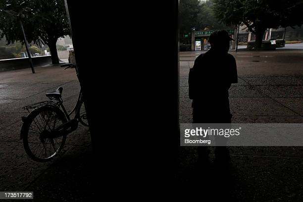 An elderly man takes shelter from rain under an awning in a park in Tokyo Japan on Monday July 8 2013 The number of Japanese seniors living alone...