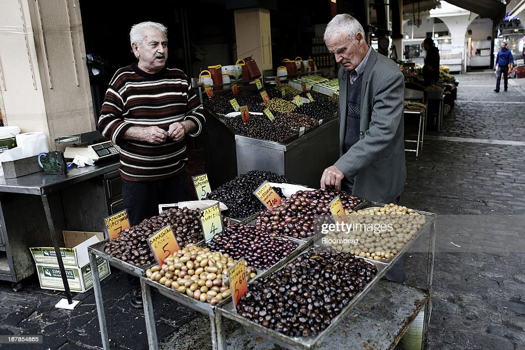 An elderly man tastes olives for sale at a trader's stall in the Kapani district market in Thessaloniki, Greece, on Wednesday, Nov. 13, 2013. Greece 'is following a fiscal adjustment program that aims to make the country's public finances sustainable on a permanent basis,' Finance Minister Yannis Stournaras told lawmakers during the debate, after holding talks with the troika earlier in the week. Photographer: Konstantinos Tsakalidis/Bloomberg via Getty Images