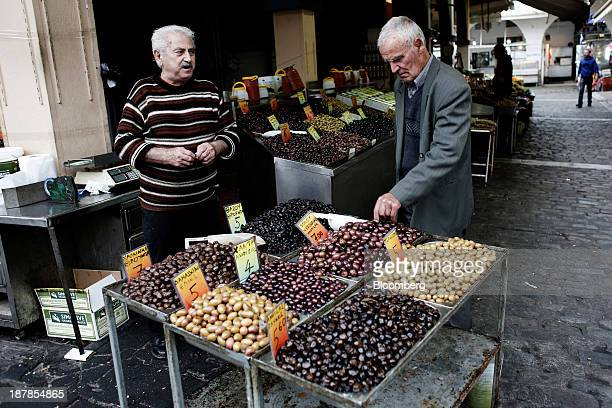An elderly man tastes olives for sale at a trader's stall in the Kapani district market in Thessaloniki Greece on Wednesday Nov 13 2013 Greece 'is...
