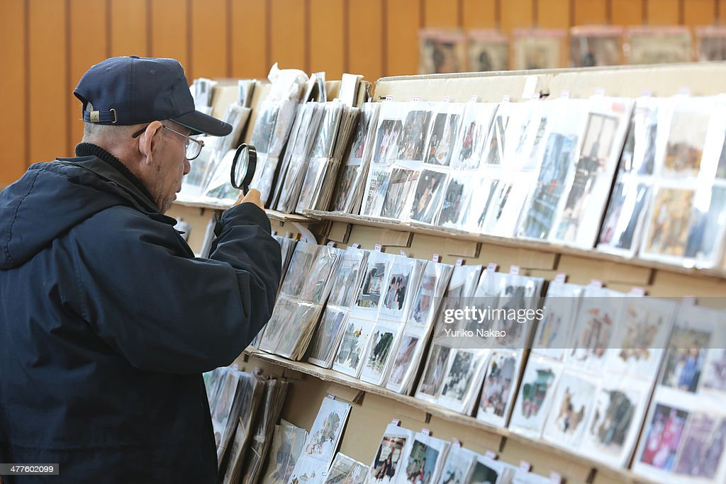 An elderly man uses a magnifying glass to look through photographs, which were repaired after being washed away by the earthquake and tsunami at a gymnasium March 10, 2014 in Sendai, Miyagi prefecture, Japan. On March 11 Japan commemorates the third anniversary of the magnitude 9.0 earthquake and tsunami that claimed more than 18,000 lives, and subsequent nuclear disaster at the Fukushima Daiichi Nuclear Power Plant.