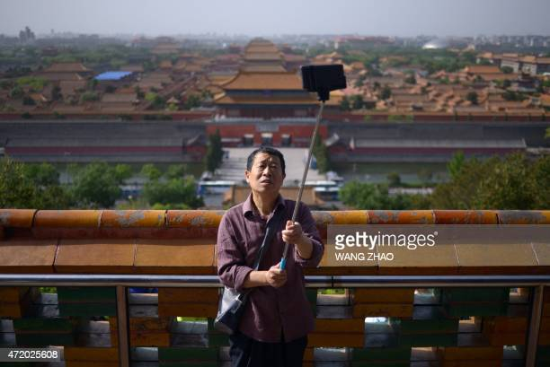 An elderly man uses a selfie stick to take a photo at a park near the Forbidden City in Beijing on May 3 2015 China will create a 'blacklist' of its...