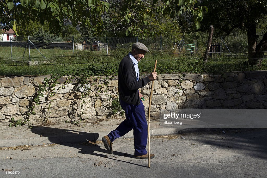 An elderly man uses a walking stick as he walks past a rural stone wall in Bohoyos, Spain, on Thursday, Sept. 26, 2013. Prime Minister Mariano Rajoy is increasingly dependent on the pension reserve fund as it reaps lower returns on Spanish sovereign debt, which comprise 97.5 percent of its investments. Photographer: Antonio Heredia/Bloomberg via Getty Images