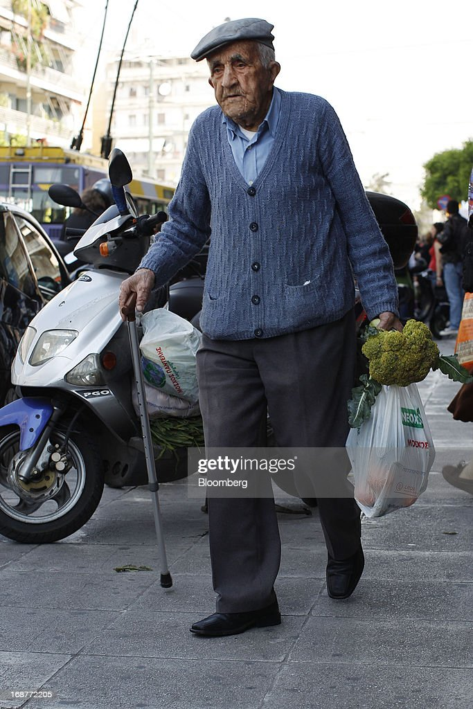 An elderly man walks away after collecting free vegetables during a handout of leftover food by striking street vendors in Athens, Greece, on Wednesday, May 15, 2013. Greece's plans to return to international bond markets next year reflect the government's confidence it can draw a line under the country's debt crisis although the cost of borrowing suggests that might be premature. Photographer: Kostas Tsironis/Bloomberg via Getty Images