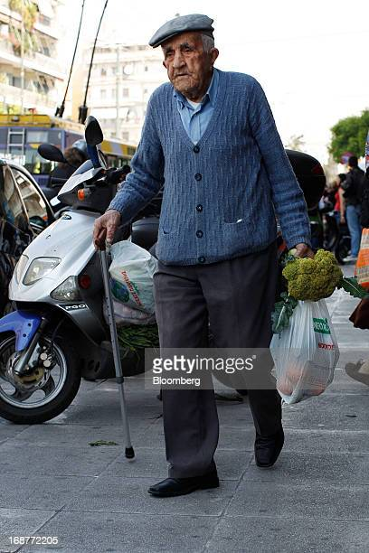An elderly man walks away after collecting free vegetables during a handout of leftover food by striking street vendors in Athens Greece on Wednesday...
