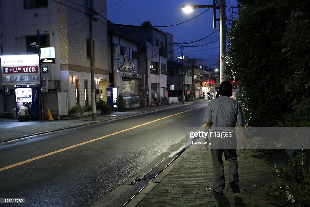 An elderly man walks down a street at night in Tokyo, Japan, on Monday, July 8, 2013. The number of Japanese seniors living alone will rise 54 percent to 7.17 million in 2030 from 4.66 million in 2010, according to the National Institute of Population and Social Security Research, set up by the Ministry of Health, Labour and Welfare. To manage the costs stemming from the aging society, the government aims to push back the pension age to 65 from 60 in stages through 2025. Photographer: Kiyoshi Ota/Bloomberg via Getty Images