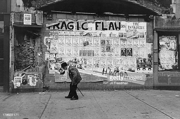 An elderly man walks on 2nd Avenue and 5th Street past billboard postings advertising bands playing at 'CBGB' New York City 1978