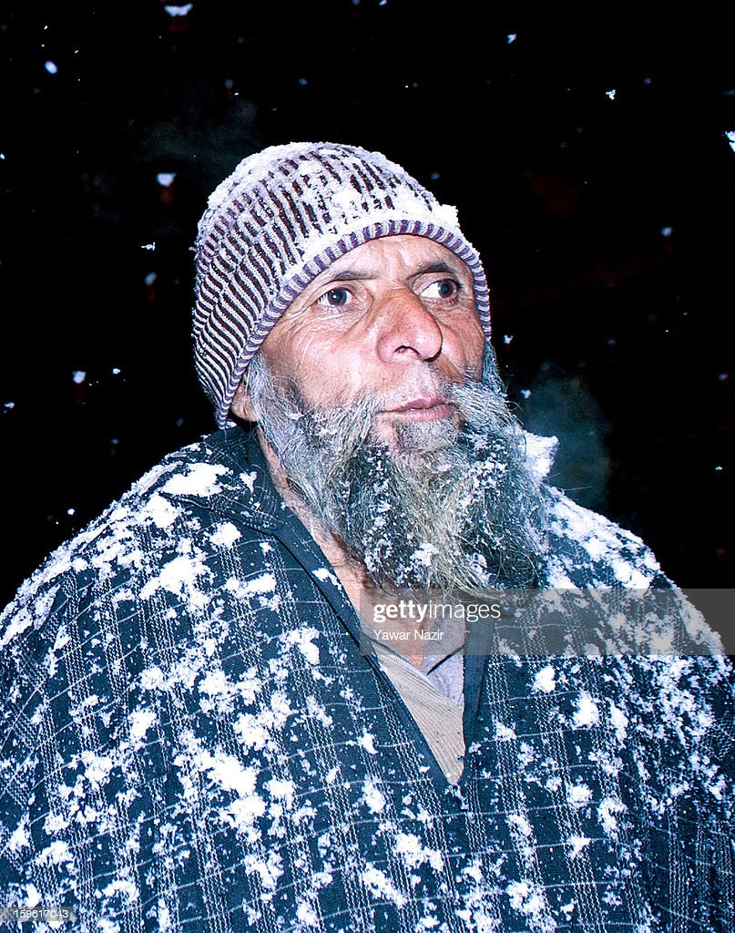 An elderly man walks on a road during heavy snowfall on January 17, 2013 in Srinagar, Indian Administered Kashmir, India. Several parts of the Kashmir Valley, including the summer capital Srinagar, experienced fresh snowfall today, prompting the authorities to issue an avalanche warning and leading to closure of the Jammu-Srinagar Highway, the only road link between Kashmir and rest of India.