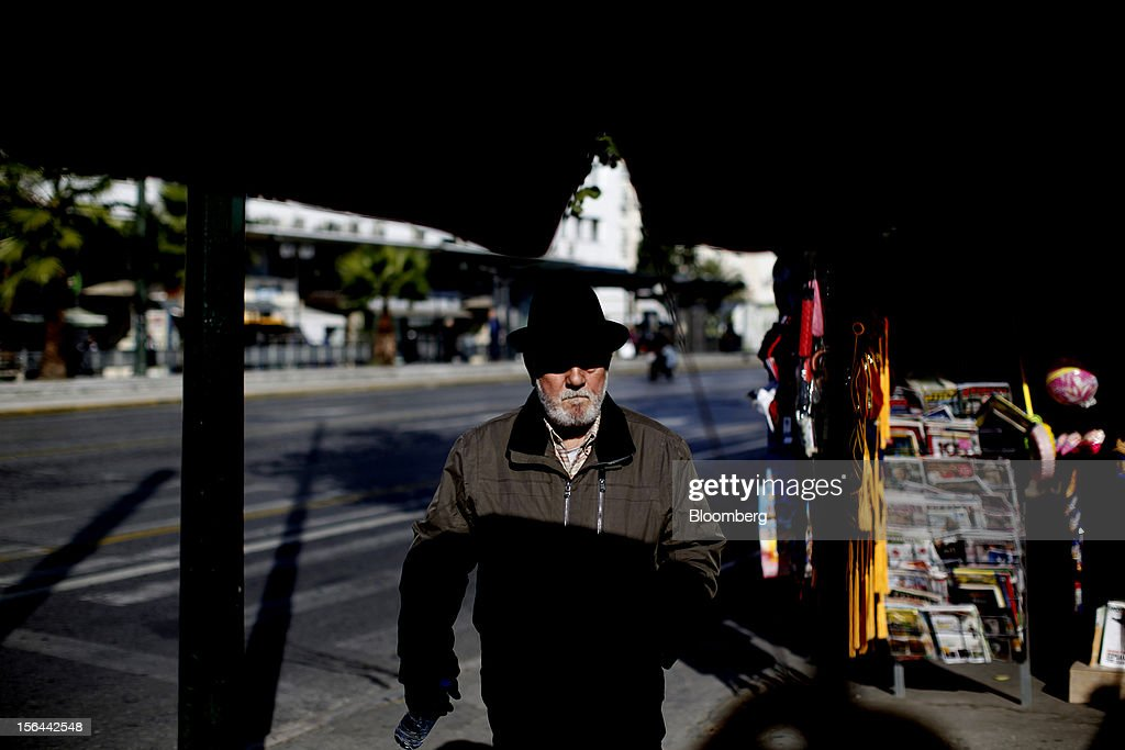 An elderly man walks past a street kiosk outside the national gardens in Athens, Greece, on Thursday, Nov. 15, 2012. Greece's Supreme Court of Audit ruled that Greek austerity measures including cuts to pensions and an increase in the retirement age may be unconstitutional, state-run Athens News Agency reports, without citing anyone. Photographer: Kostas Tsironis/Bloomberg via Getty Images