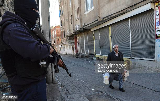 An elderly man walks past an armed government soldier during clashes in central Diyarbakir on March 17 2016 Turkish security forces clashed with...