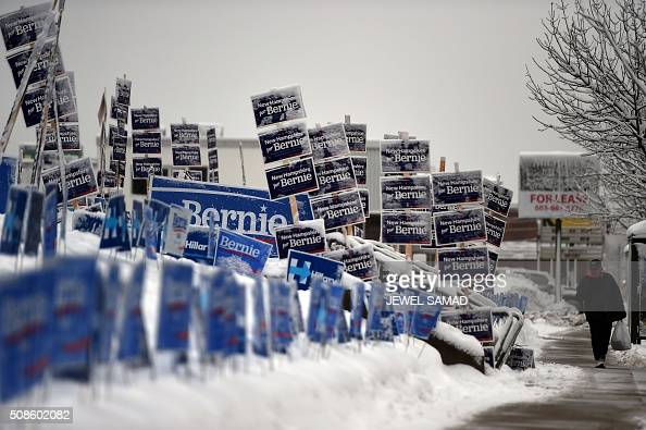 An elderly man walks past campaign signs of US Democratic presidential candidates Hillary Clinton and Bernie Sanders in Manchester New Hampshire on...