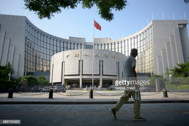 An elderly man walks past the People's Bank of China in Beijing on August 12 2015 China cut the yuan's value against the US dollar for the second...