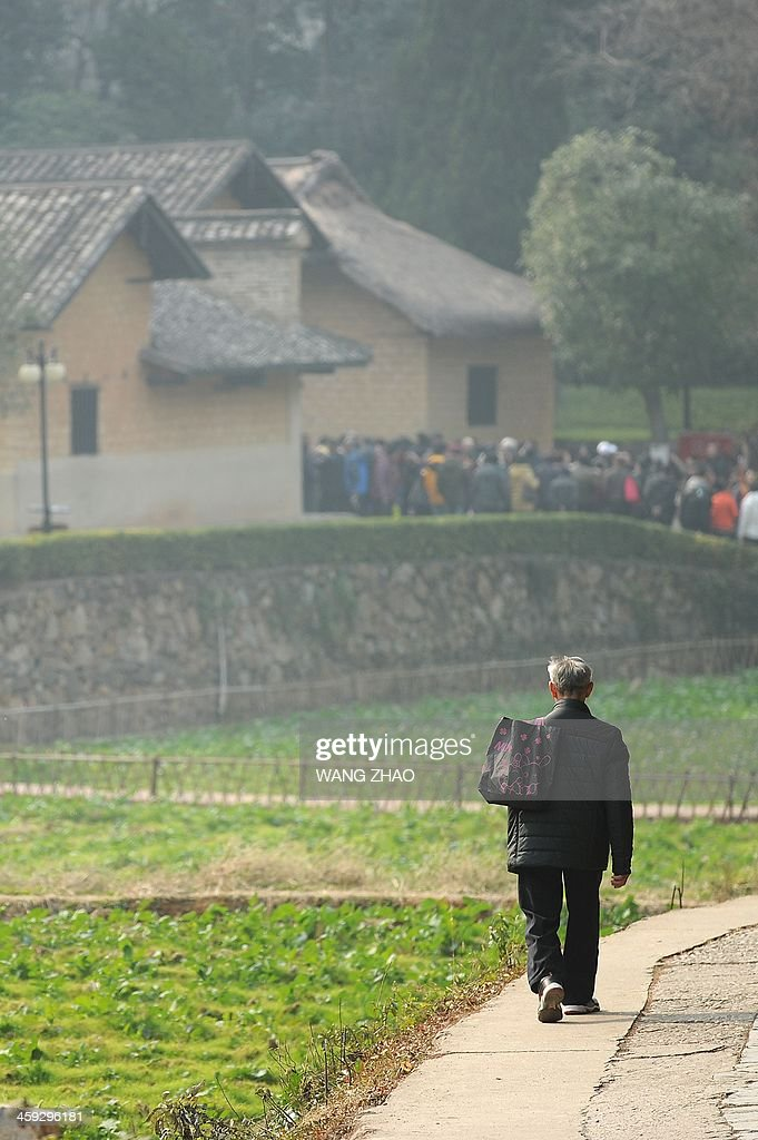 An elderly man walks toward to the former residence of the former Chinese leader Mao Zedong in Shaoshan, in China's central province of Hunan on December 25, 2013. Thousands of admirers of Communist China's founder Mao Zedong flocked to his home town on December 25 to bow before his graven image -- including one statue of solid gold -- before the 120th anniversary of his birth.