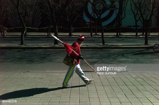 TOPSHOT An elderly man walks with a traditional spear under his arm after his morning exercise in Beijing on February 10 2017 / AFP PHOTO / Fred...