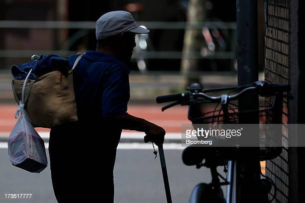 An elderly man walks with a walking stick as he carries clothes and a box of detergent to a laundromat in Tokyo Japan on Monday July 8 2013 The...