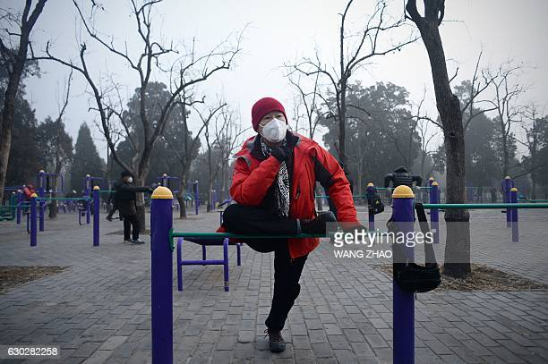 TOPSHOT An elderly man wearing a mask exercises at a park in Beijing on December 20 2016 Heavy smog suffocated northeast China for a fifth day on...