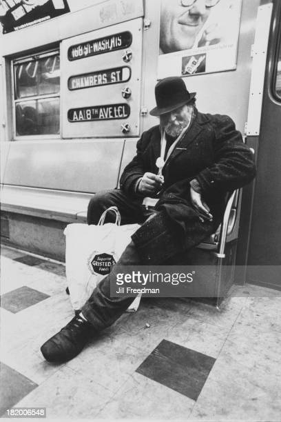 An elderly man wearing a winter coat and holding a lollipop on a subway train New York City circa 1968
