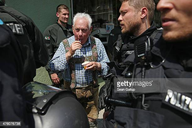 An elderly man wearing Lederhosen eats icecream as riot police walk past during a march by antiG7 protesters through the city center the day before...