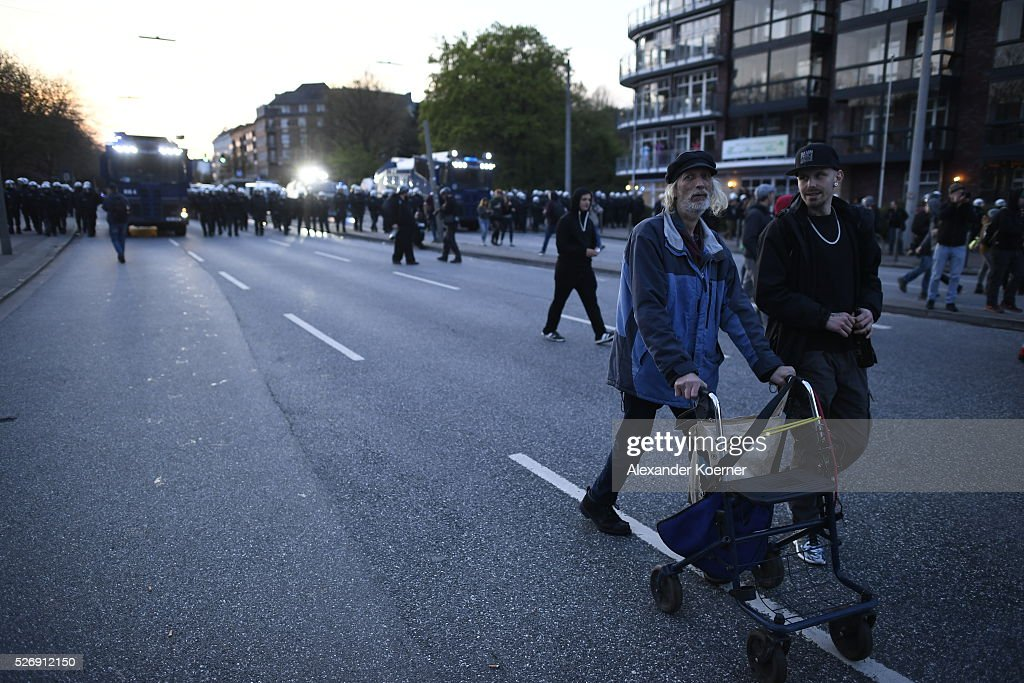 An elderly men walks beside leftist protesters after clashing with police forces on May Day on 01 May, 2016 in Hamburg, Germany. Tens of thousands of people across Germany participated in marches and gatherings by labor unions and in some cities left-wing and anarchist activists took to the streets under heavy oversight by police.