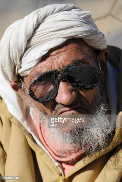 An elderly Moroccan villager wearing homemade sunglasses sits outside his house in Anfgou in the High Atlas mountains on January 12 2013 More than 20...