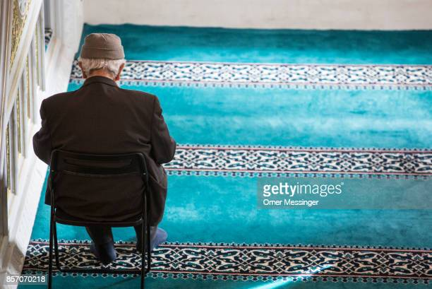 An elderly Muslim man is seen sitting on a chair during midday prayers at Sehitlik mosque which is mostly Turkish on Open Mosque Day on October 3...