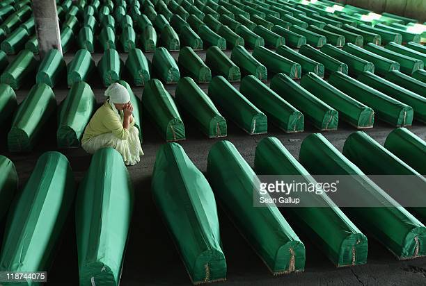 An elderly Muslim woman weeps over a coffin among 613 coffins of victims of the 1995 Srebrenica massacre in a hall at the Potocari cemetery and...