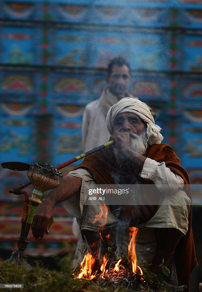 An elderly Pakistani man smokes a hookah at the roadside in Lahore on January 30, 2013. Year-on-year inflation stood at 6.9 percent in November, the State Bank of Pakistan said in a statement, a faster fall than had been estimated. Food inflation dropped to 5.3 percent and non-food inflation to 8.1 percent. AFP PHOTO/Arif ALI