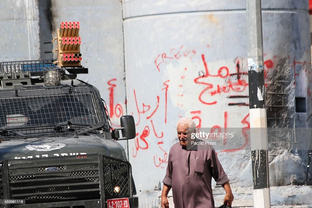 An elderly Palestinian man makes his way home to Aida Refugee camp in Bethlehem, as an Israeli army jeep is parked behind him. The Islamic Jihad faction organized protests in solidarity with Gaza, in the West Bank city of Bethlehem. As ceasefire talks collapsed completely in Cairo earlier this week, and fighting renewed on Wednesday. Hamas launched a barrage of rockets towards Southern Israel, some reaching as far as Jerusalem and illegal Israeli settlements in the West Bank, some 80 kilometers away from Gaza. Late Tuesday evening an Israeli missile struck the home of Hamas military commander Muhammad Deif, killing his wife and three-year-old daughter. Deif, according to Hamas reports was not assassinated. On Thursday, three more to military commanders, Muhammad Abu Shammala, Raed al-Attar and Muhammad Barhoum were also killed in airstrikes. In response, Hamas killed what they believed to be collaborators with Israel in Gaza. 18 suspected of having worked with Israeli army intelligence have been killed so far. Late Friday afternoon, a four-year-old Israeli child from Nihal Oz was killed by mortar fire from Gaza. To date, the death toll from the Gaza war stands at 2090 Palestinians and 67 Israelis.