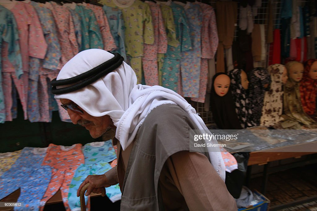 An elderly Palestinian man passes by a stall selling womens' and childrens' clothing in the Muslim Quarter of the Old City on October 22, 2009 in Jerusalem. Israel categorically denied Palestinian claims that its archaeologists are conducting digs underneath al-Aqsa mosque.