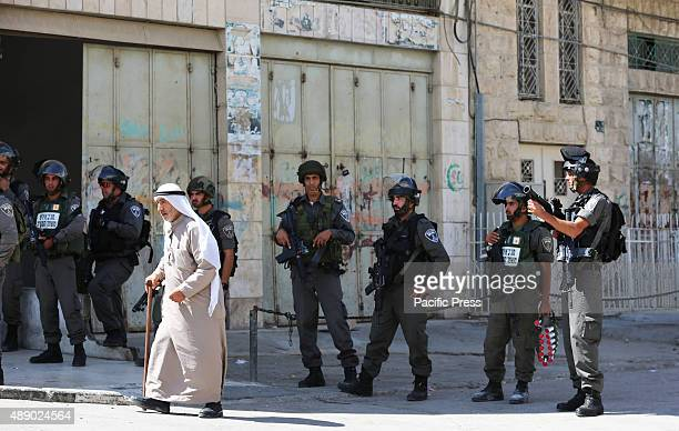 An elderly Palestinian man passes Israeli soldiers during a demonstration in the West Bank city of Hebron In the West Bank city of Hebron hundreds of...