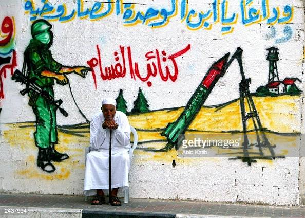 An elderly Palestinian man sits in front of a wall with a mural showing a masked militant from Ezz ElDeen AlQassam Martyrs' Brigade the military wing...