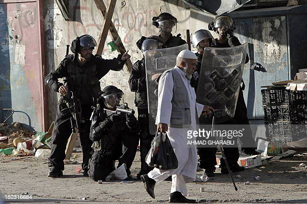 An elderly Palestinian man walks past Israeli border policemen as they take position during clashes that erupted with Palestinian protesters after a...