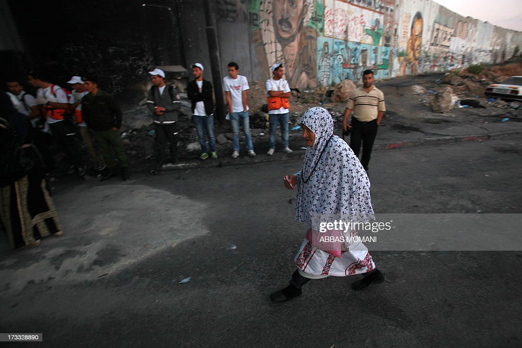 An elderly Palestinian Muslim woman arrives to cross the Qalandia checkpoint between Ramallah and Jerusalem on her way to attend the first Friday prayers of Ramadan in the Al-Aqsa mosque compound on July 12, 2013. AFP PHOTO/ABBAS MOMANI