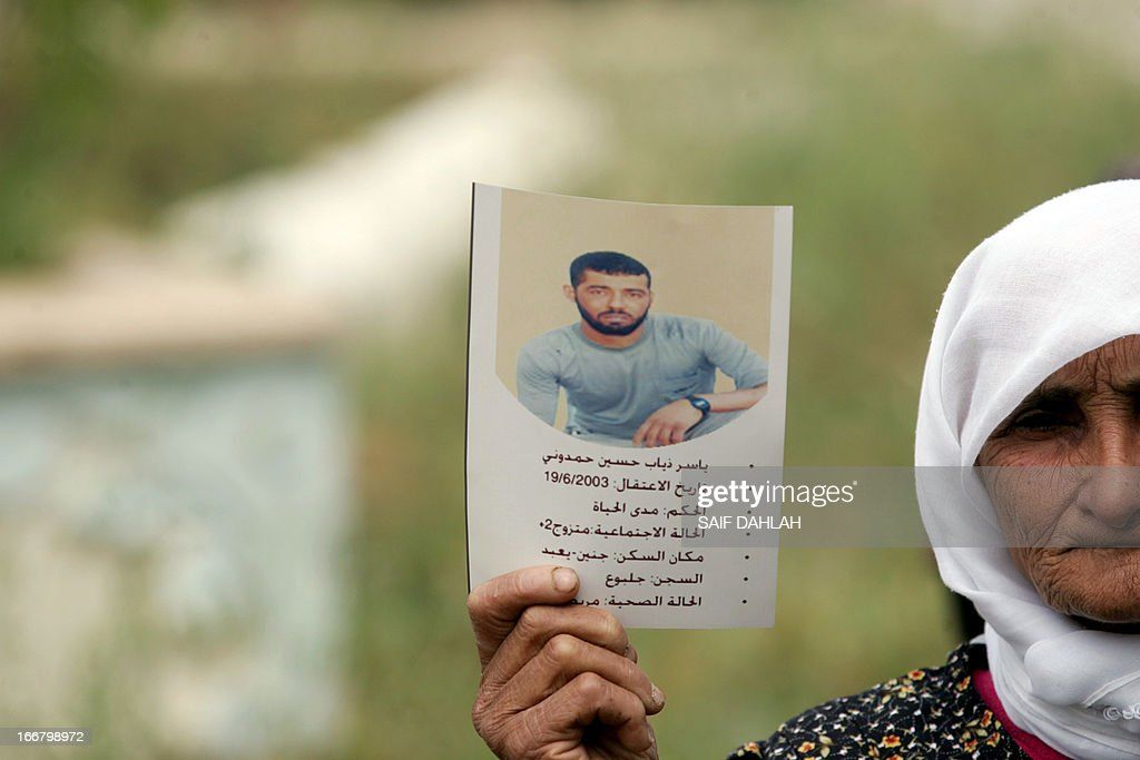 An elderly Palestinian woman carries a placard with the information of a prisoner during a gathering to commemorate Prisoners' Day in the West Bank city of Jenin on April 17, 2013. Palestinians across the territories are attending marches and rallies as a show of solidarity with prisoners from the West Bank, east Jerusalem and Gaza held in Israeli facilities, whose numbers according to Israeli rights group B'Tselem reach 4,713.