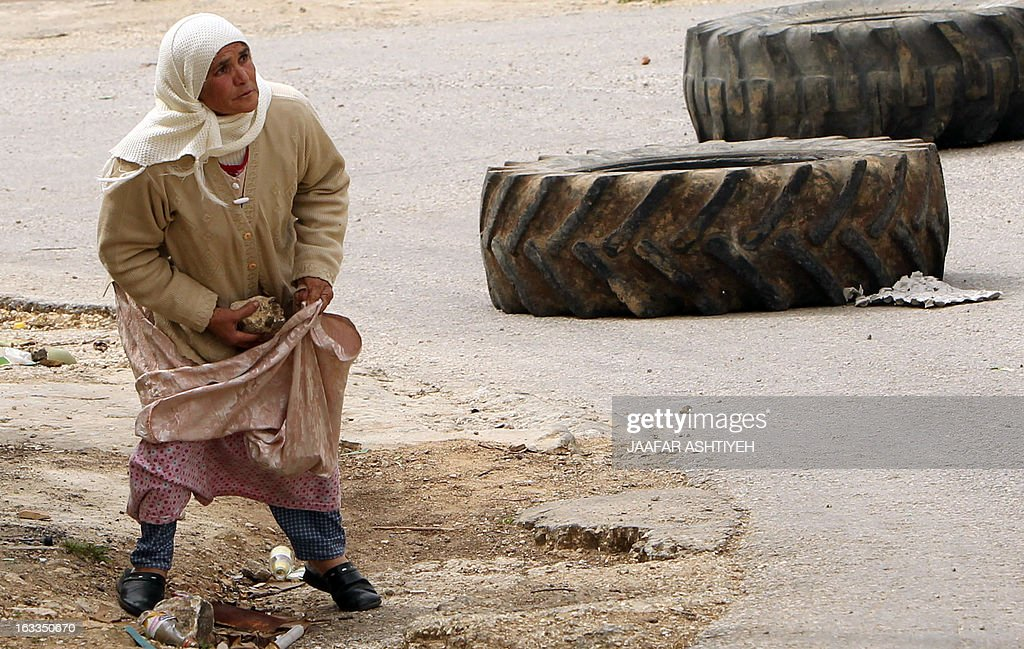 An elderly Palestinian woman collects stones to throw towards Israeli security forces during clashes following a protest against the expropriation of Palestinian land by Israel on March 8, 2013, in the village of Kafr Qaddum, near the occupied West Bank city of Nablus. AFP PHOTO/JAAFAR ASHTIYEH