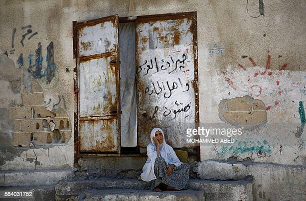 TOPSHOT An elderly Palestinian woman sits in front of her house in Gaza City on July 28 2016 / AFP / MOHAMMED ABED