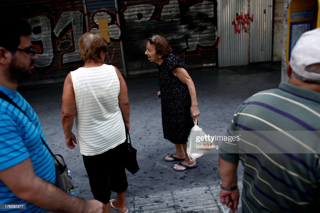 An elderly pedestrian carries a plastic shopping bag on a street outside the meat market in Athens, Greece, on Saturday, Aug. 10, 2013. Greece's economy contracted for a 20th quarter, extending an economic slump that has left more than six in 10 young Greeks out of work. Photographer: Angelos Tzortzinis/Bloomberg via Getty Images